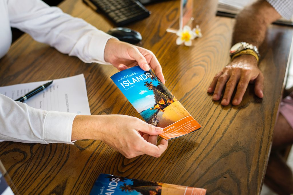Travel agent passing a leaflet to a customer over the desk